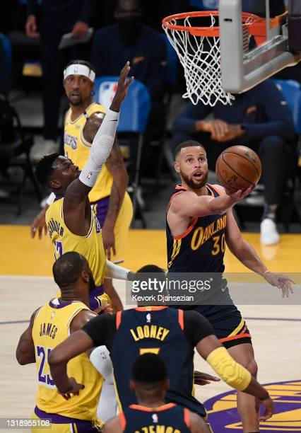 Stephen Curry of the Golden State Warriors goes to the basket as Dennis Schroder of the Los Angeles Lakers defends during the first half of an NBA...