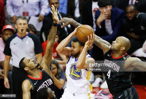 Stephen Curry of the Golden State Warriors goes up against Trevor Ariza and PJ Tucker of the Houston Rockets in the fourth quarter of Game Seven of...