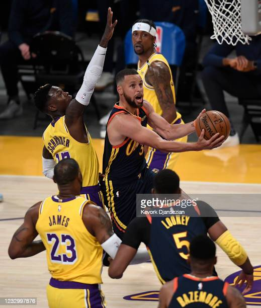Stephen Curry of the Golden State Warriors goes up for a layup against Dennis Schroder of the Los Angeles Lakers during the first half of an NBA...