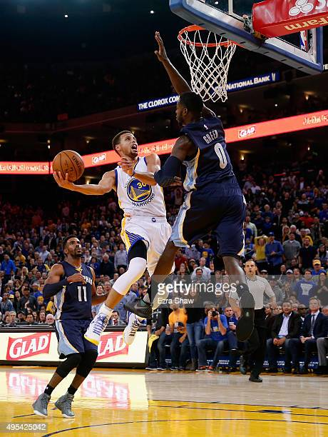 Stephen Curry of the Golden State Warriors goes up for a shot against JaMychal Green and Mike Conley of the Memphis Grizzlies at ORACLE Arena on...