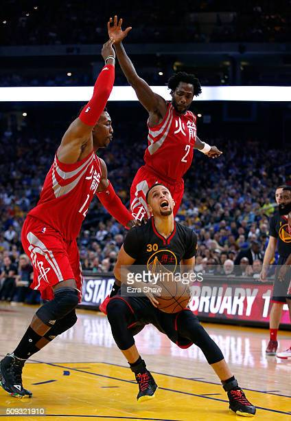 Stephen Curry of the Golden State Warriors goes up for a shot against Dwight Howard and Patrick Beverley of the Houston Rockets at ORACLE Arena on...