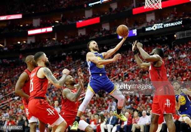 Stephen Curry of the Golden State Warriors goes up for a shot defended by James Harden of the Houston Rockets and PJ Tucker in the fourth quarter...