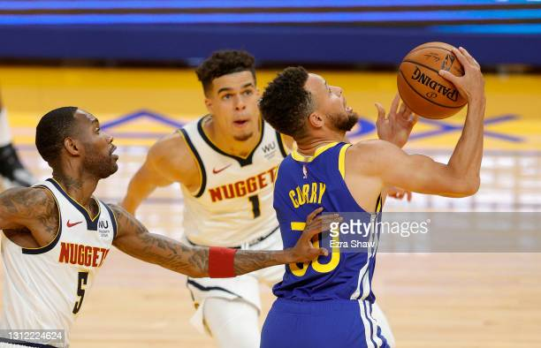 Stephen Curry of the Golden State Warriors goes up for a shot on Michael Porter Jr. #1 and Will Barton of the Denver Nuggets at Chase Center on April...