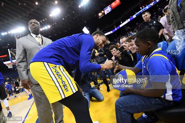 Stephen Curry of the Golden State Warriors greets fan before the game against the Indiana Pacers on March 21 2019 at ORACLE Arena in Oakland...