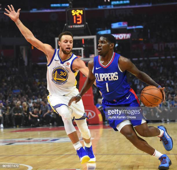 Stephen Curry of the Golden State Warriors guards Jawun Evans of the Los Angeles Clippers as he drives to the basket in the first half of the game on...