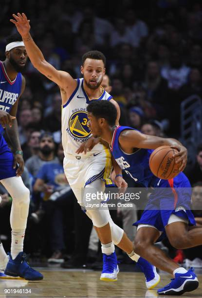 Stephen Curry of the Golden State Warriors guards Jawun Evans of the Los Angeles Clippers as he drives to the basket in the second half of the game...
