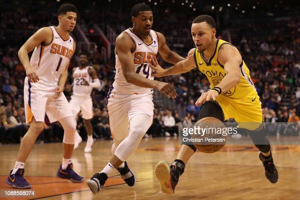 Stephen Curry of the Golden State Warriors handles the ball against De'Anthony Melton of the Phoenix Suns during the first half of the NBA game at...