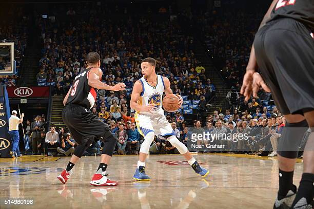 Stephen Curry of the Golden State Warriors handles the ball against CJ McCollum of the Portland Trail Blazers on March 11 2016 at Oracle Arena in...