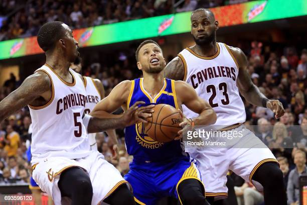 Stephen Curry of the Golden State Warriors handles the ball against JR Smith and LeBron James of the Cleveland Cavaliers in the second quarter in...