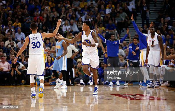 Stephen Curry of the Golden State Warriors high fives Brandon Rush of the Golden State Warriors during their game against the Denver Nuggets at...