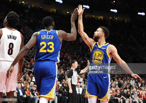 Stephen Curry of the Golden State Warriors high fives Draymond Green during the first half against the Portland Trail Blazers in game three of the...