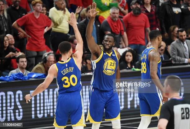 Stephen Curry of the Golden State Warriors high fives Draymond Green during the second half against the Portland Trail Blazers in game four of the...