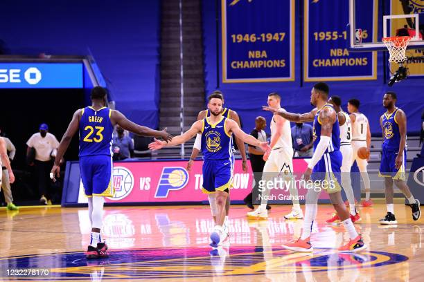 Stephen Curry of the Golden State Warriors high fives Draymond Green and Kent Bazemore during the game against the Denver Nuggets on April 12, 2021...