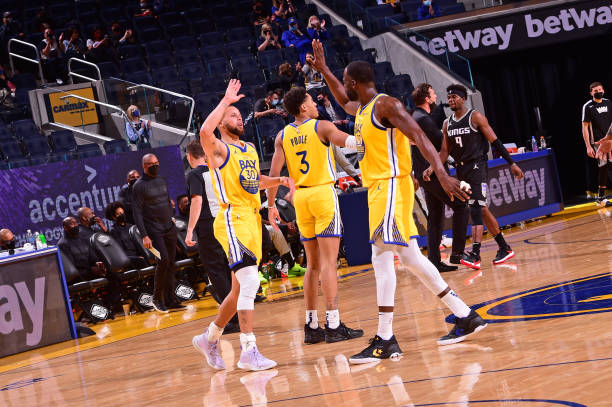 Stephen Curry of the Golden State Warriors high fives Draymond Green of the Golden State Warriors during the game against the Sacramento Kings on...