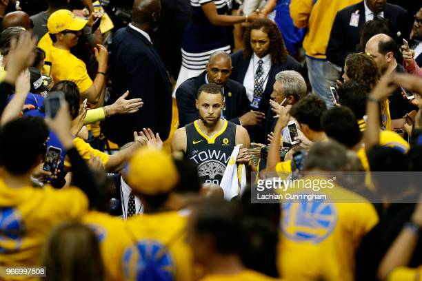 Stephen Curry of the Golden State Warriors high fives fans as he leaves the floor after they defeated the Cleveland Cavaliers in Game 2 of the 2018...