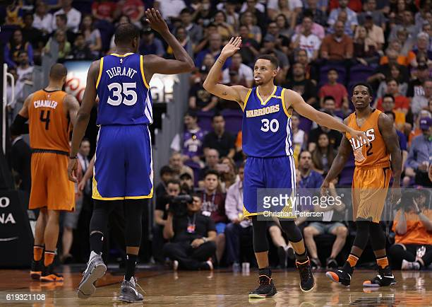 Stephen Curry of the Golden State Warriors high fives Kevin Durant after scoring against the Phoenix Suns during the second half of the NBA game at...