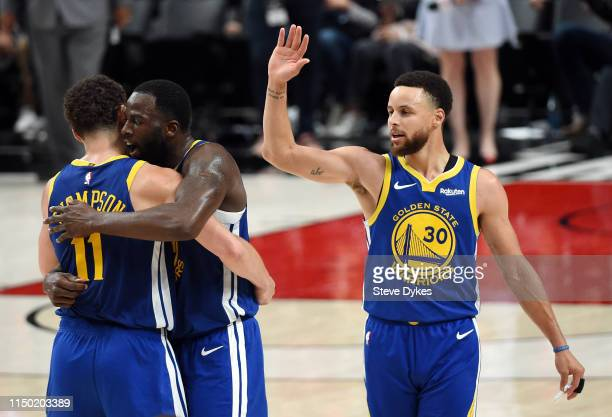 Stephen Curry of the Golden State Warriors high fives teammates during the second half against the Portland Trail Blazers in game three of the NBA...