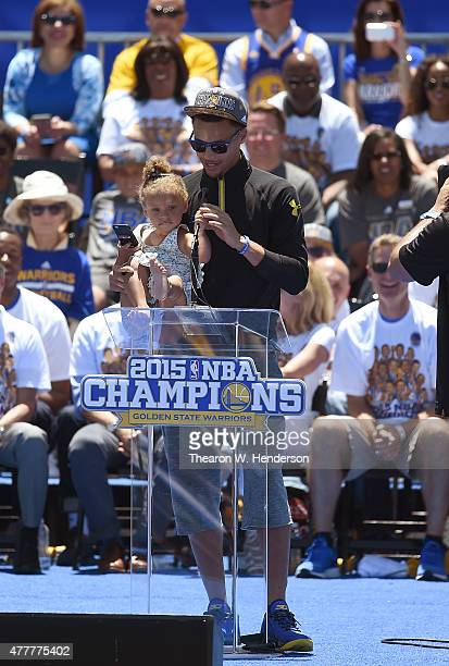 Stephen Curry of the Golden State Warriors holds his daughter Riley Curry while he talks to the fans as they celebrate the Warriors 2015 NBA...