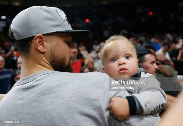 Stephen Curry of the Golden State Warriors holds his son Canon W Jack Curry after defeating the Portland Trail Blazers 119117 during overtime in game...