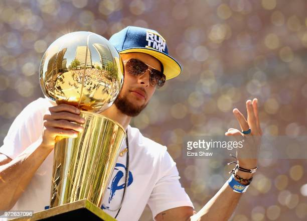 Stephen Curry of the Golden State Warriors holds the championship trophy during the Golden State Warriors Victory Parade on June 12 2018 in Oakland...