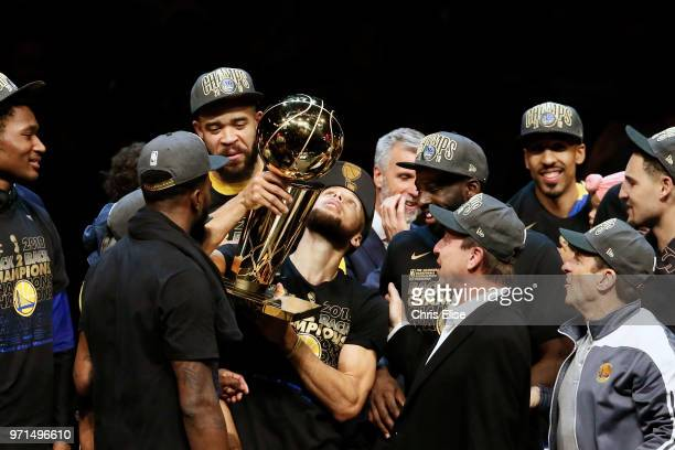 Stephen Curry of the Golden State Warriors holds the Larry O'Brien Championship trophy after defeating the Cleveland Cavaliers in Game Four of the...