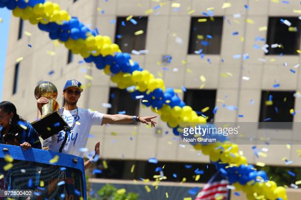 Stephen Curry of the Golden State Warriors holds the Larry O'Brien Championship trophy during the Golden State Warriors Victory Parade on June 12...