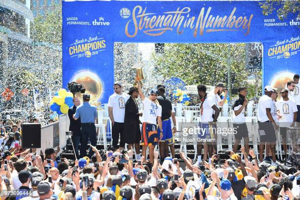 Stephen Curry of the Golden State Warriors holds up the Larry O'Brien Championship Trophy on stage during the Golden State Warriors Victory Parade on...