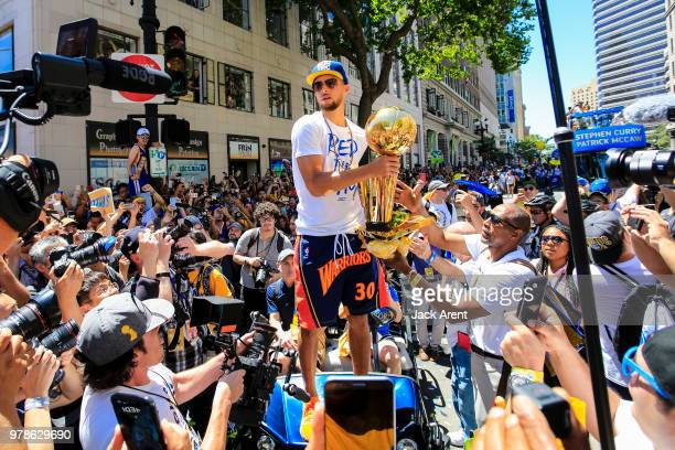 Stephen Curry of the Golden State Warriors holds up the Larry O'Brien Championship Trophy with fans during the Victory Parade on June 12 2018 in...