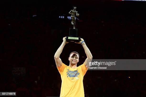 Stephen Curry of the Golden State Warriors holds up the Maurice Podoloff MVP trophy before the game against the Portland Trail Blazers in Game Five...