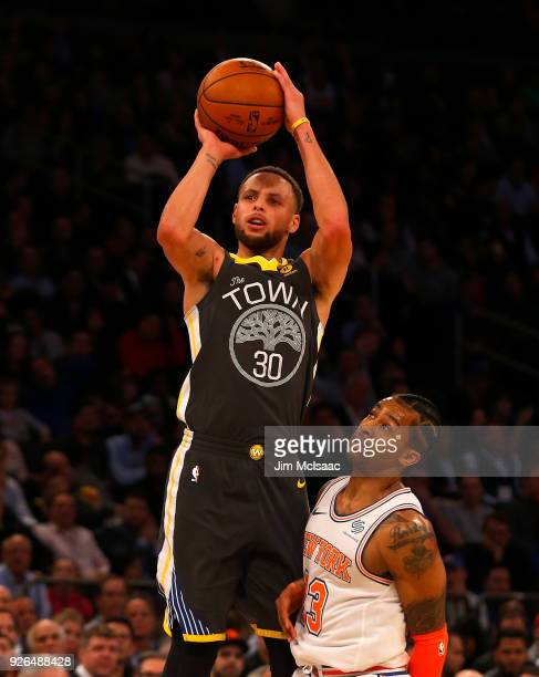 Stephen Curry of the Golden State Warriors in action against Trey Burke of the New York Knicks at Madison Square Garden on February 26 2018 in New...