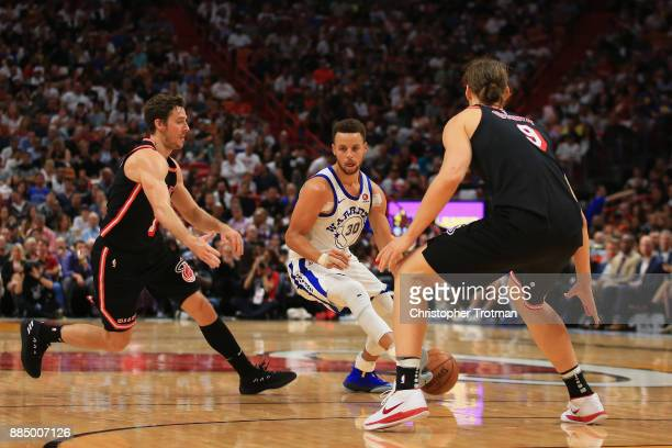 Stephen Curry of the Golden State Warriors is challenged by Kelly Olynyk of the Miami Heat and Goran Dragic of the Miami Heat and at American...