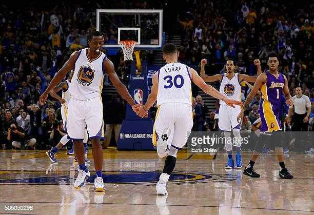 Stephen Curry of the Golden State Warriors is congratulated by Harrison Barnes and Shaun Livingston after he dunked the ball against the Los Angeles...