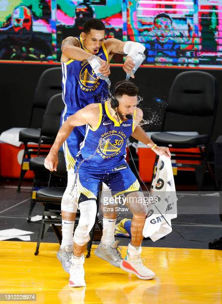 Stephen Curry of the Golden State Warriors is doused with water by Juan Toscano-Anderson of the Golden State Warriors after their win over the Denver...