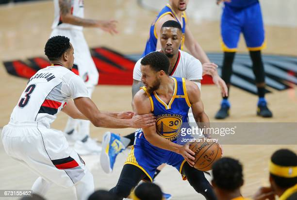 Stephen Curry of the Golden State Warriors is guarded by CJ McCollum and Damian Lillard of the Portland Trail Blazers during Game Four of the Western...