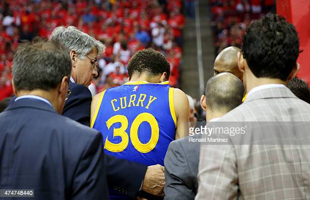 Stephen Curry of the Golden State Warriors is helped off of the court after being injured in the second quarter against the Houston Rockets during...