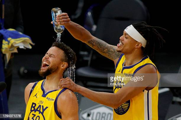 Stephen Curry of the Golden State Warriors is showered in water by Damion Lee of the Golden State Warriors during a post-game interview after Curry...