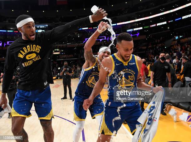 Stephen Curry of the Golden State Warriors is showered with water by his teammates Gary Payton II and Damion Lee as they celebrate after defeating...