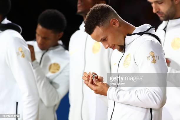 Stephen Curry of the Golden State Warriors looks at his 2017 NBA Championship ring prior to their NBA game against the Houston Rockets at ORACLE...