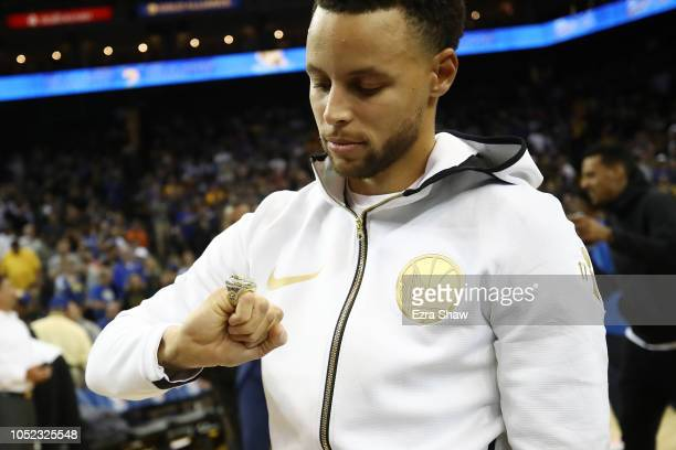 Stephen Curry of the Golden State Warriors looks at his 20172018 Championship ring prior to their game against the Oklahoma City Thunder at ORACLE...