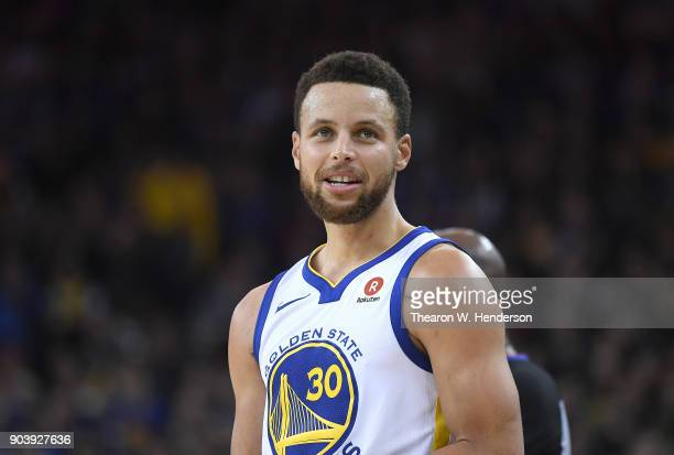 Stephen Curry of the Golden State Warriors looks on against the Denver Nuggets during an NBA Basketballl game at ORACLE Arena on January 8 2018 in...