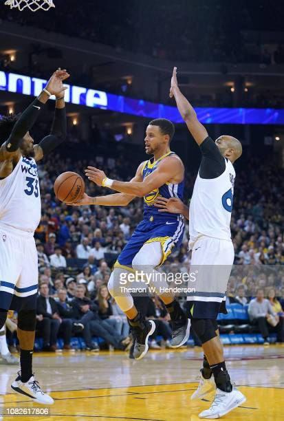Stephen Curry of the Golden State Warriors looks to get a shot off over Robert Covington and Taj Gibson of the Minnesota Timberwolves during an NBA...