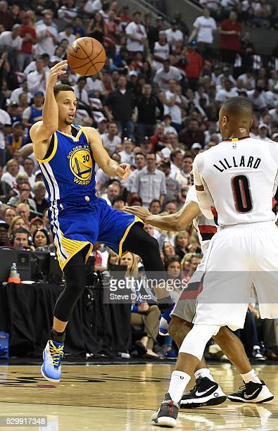 Stephen Curry of the Golden State Warriors looks to pass the ball as Damian Lillard of the Portland Trail Blazers defends during the first quarter of...