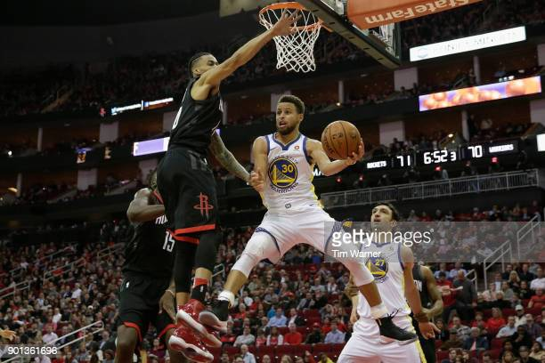 Stephen Curry of the Golden State Warriors looks to pass under the basket defended by Gerald Green of the Houston Rockets in the second half at...