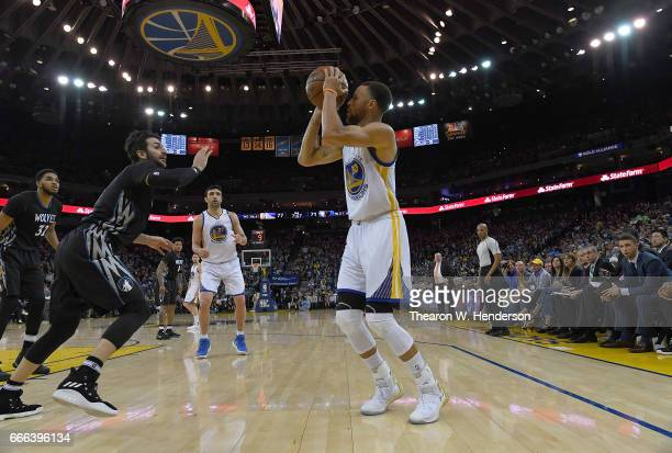 Stephen Curry of the Golden State Warriors looks to shoot the ball over Ricky Rubio of the Minnesota Timberwolves during an NBA basketball game at...