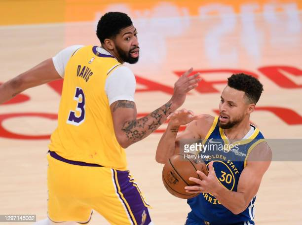 Stephen Curry of the Golden State Warriors loses control of the ball as he is guarded by Anthony Davis of the Los Angeles Lakers during a 115-113...