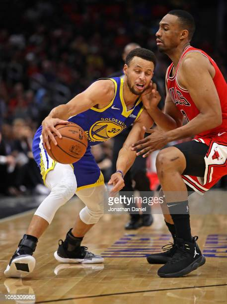 Stephen Curry of the Golden State Warriors moves against Jabari Parker of the Chicago Bulls at the United Center on October 29 2018 in Chicago...