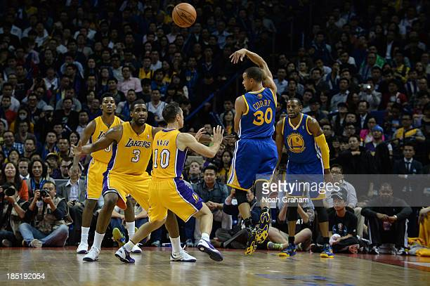 Stephen Curry of the Golden State Warriors passes against Steve Nash of the Los Angeles Lakers during the 2013 Global Games on October 18 2013 at the...