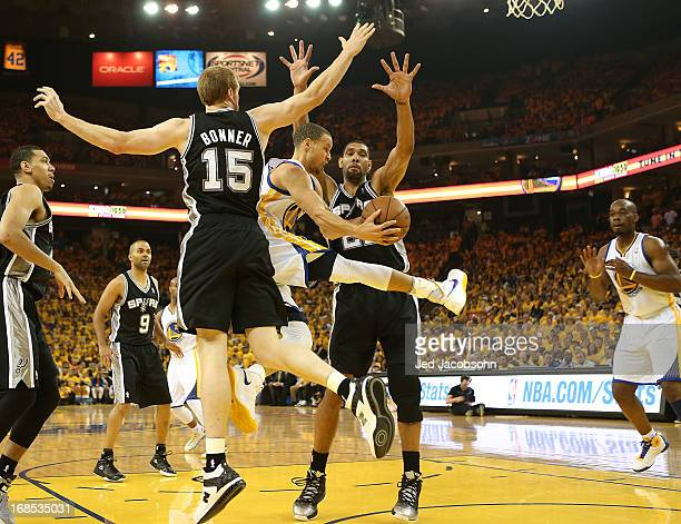 Stephen Curry of the Golden State Warriors passes against Tim Duncan and Matt Bonner of the San Antonio Spurs in Game Three of the Western Conference...