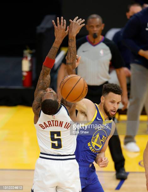 Stephen Curry of the Golden State Warriors passes around Will Barton of the Denver Nuggets at Chase Center on April 12, 2021 in San Francisco,...