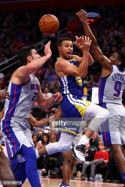 Stephen Curry of the Golden State Warriors passes from between the defense of Langston Galloway and Zaza Pachulia of the Detroit Pistons during the...